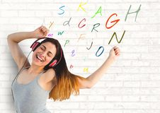 Young woman listening music with colour letters around. Digital composite of young woman listening music with colour letters around Royalty Free Stock Image