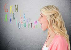 Young woman shouting with colour letters coming up from mouth Royalty Free Stock Photos