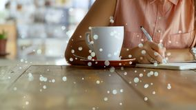 Woman writing on her notebook against bokeh effect. Digital composite of a young woman writing on her notebook on a wooden table in a café against the white stock video