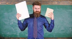 Digital contre le papier Le hippie barbu de professeur tient le livre et l'ordinateur portable Ce qui vous préférerait Choix de p photographie stock libre de droits