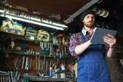Digital Control in Auto Maintenance Garage. Low angle portrait of handsome mechanic using tablet to check auto systems in repair workshop Stock Photos