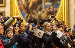 Digital Crowd. Paris,France-  December 19, 2011: Image of a crowd of people using various digital devices to photograph important paintings Mona Lisa by Leonardo Stock Photos