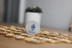 Grey Ethereum token. Digital currency physical grey ethereum token on gold bitcoin coins near flower Stock Image