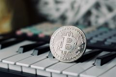 Bitcoin and music keyboard. Digital currency physical metal bitcoin coin and music keyboard. Cryptocurrency sound concept royalty free stock photography