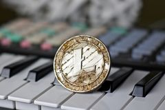 Litecoin and music keyboard. Digital currency physical metal litecoin coin and music keyboard. Cryptocurrency music concept royalty free stock images