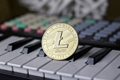 Litecoin and music keyboard. Digital currency physical metal litecoin coin and music keyboard. Cryptocurrency music concept stock image
