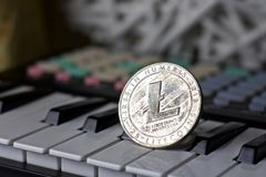 Litecoin and music keyboard. Digital currency physical metal litecoin coin and music keyboard. Cryptocurrency music concept royalty free stock photo