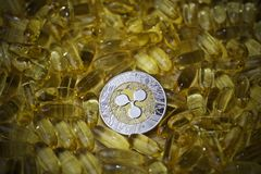 Ripple coin in yellow drugs. Digital currency physical metal ripple coin. Cryptocurrency drugs concept stock images