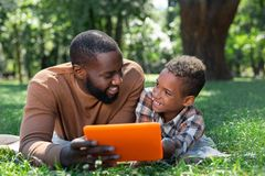 Delighted nice man holding a modern tablet. Digital device. Delighted nice men holding a modern tablet while showing a picture to his son royalty free stock photography