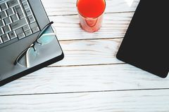 Digital device, glasses, laptop and carrot juice work place, toned. Digital device, glasses, laptop and carrot juice work place Royalty Free Stock Photography