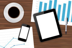 Digital Devices and Financial Charts with Coffee. Top view of modern business workplace, digital tablet and smart phone with white blank empty screen, pen, cup Royalty Free Stock Images