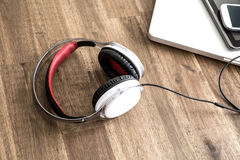 Digital devices and Headphones on a wooden Desktop Stock Photo