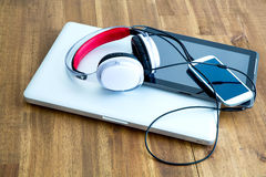 Digital devices and Headphones on a wooden Desktop Royalty Free Stock Images