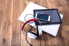Digital devices and Headphones on a wooden Desktop Royalty Free Stock Photo