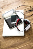 Digital devices and Headphones on a wooden Desktop Stock Image