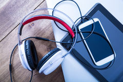 Digital devices and Headphones on a wooden Desktop Stock Photography