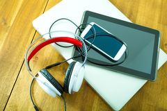 Digital devices and Headphones on a wooden Desktop Royalty Free Stock Image