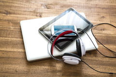 Digital devices and Headphones on a wooden Desktop Royalty Free Stock Photos