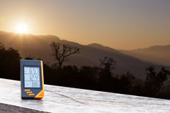 Digital display thermometer with mountain and sunlight Stock Photo