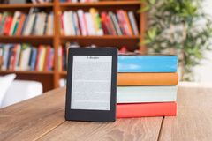 Digital-eBook Leser und Papierbücher auf Tabelle stockbilder