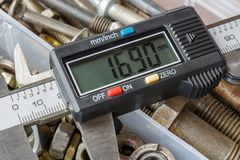 Digital electronic caliper on a background of rusty used bolts and nuts in storage box closeup royalty free stock photos