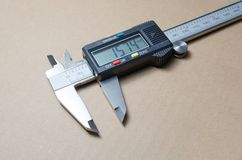 Digital electronic vernier caliper. On a brown background royalty free stock image