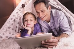 Joyful caring father holding a tablet royalty free stock photos
