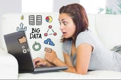 Digital erzeugtes Bild der überraschten Frau, die Laptop mit großen Daten verwendet, stellen zu Hause grafisch dar lizenzfreie stockfotografie
