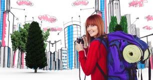 Digital erzeugtes Bild der weiblichen touristischen haltenen Kamera mit Gebäuden und Bäumen im Hintergrund Stockfotos