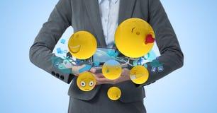 Digital erzeugtes Bild von buisnesswoman mit Laptop und von smileygesicht emoji gegen blauen Hintergrund Stockfotografie