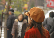 Digital fashion. Girl listening to a discreet earphone in a crowded city street Stock Images