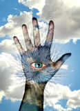 Digital fingerprint concept. Hand with digital imprint of eye on palm raised up with blue sky and cloudscape background Royalty Free Stock Photos