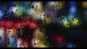 Digital frambragda regndroppar, som faller på ett dimmigt fönster på natten, då det regnar, och bakgrunden göras suddig lager videofilmer