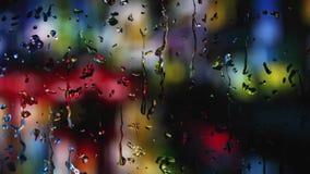 Digital frambragda regndroppar, som faller på ett dimmigt fönster på natten, då det regnar, och bakgrunden göras suddig stock video