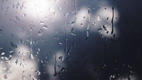 Digital frambragda regndroppar, som faller på ett dimmigt fönster under dagen, då det regnar, och bakgrunden göras suddig arkivfilmer