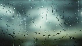 Digital frambragda regndroppar, som faller på ett dimmigt fönster under dagen, då det regnar, och bakgrunden göras suddig stock video