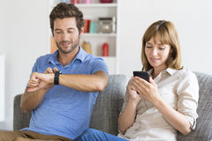 Digital geek couple. Mobile phone, smart watch. Modern white apartment Royalty Free Stock Photos