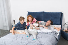 Digital-Gläser der Tochter-tragende virtuellen Realität, die mit Eltern und Bruder On Bed, Familie hat Spaß sitzen stockfotografie