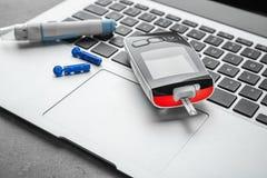 Digital glucometer and lancet pen on laptop. Diabetes management Royalty Free Stock Photos
