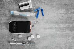 Digital glucometer, lancet pen, syringe and medicaments. On grey background. Diabetes management Stock Photography