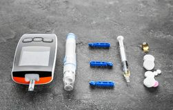 Digital glucometer, lancet pen, syringe. And medicaments on grey background. Diabetes management Stock Photo