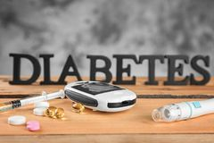 Digital glucometer, medicaments and blurred word. `Diabetes` on background Royalty Free Stock Photo
