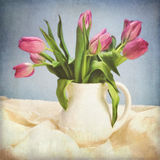 Digital Grunged Tulip Painting. A digital still life painting of pink tulips in a white pitcher sitting on white fabric with a blue background Stock Images