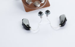 Digital hearing aids. Two digital hearing aids with a pack of batteries isolated on a white background Stock Images