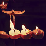 Digital illustration of three candles on dark background. Home altar or church. Wax melting under fire Stock Photo