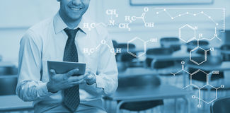 Composite image of digital image of chemical formulas. Digital image of chemical formulas against teacher with tablet pc in the class room royalty free stock image