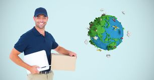 Digital image of delivery man holding box and writing pad while standing by planet earth against blu. Digital composite of Digital image of delivery man holding Stock Photos