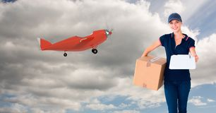 Digital image of female delivering parcel standing by airplane on sky. Digital composite of Digital image of female delivering parcel standing by airplane on sky stock images