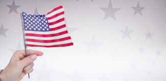 Digital image of hand holding American flag. Against starry background Royalty Free Stock Photography