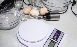 Digital-Küchenskalen und -schüsseln auf einer weißen Tabelle stockfotografie